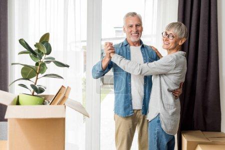 Photo pour Homme mûr et femme souriante dansant dans une nouvelle maison - image libre de droit