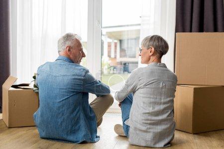 Photo pour Vue arrière de l'homme et de la femme matures assis sur le sol dans une nouvelle maison - image libre de droit