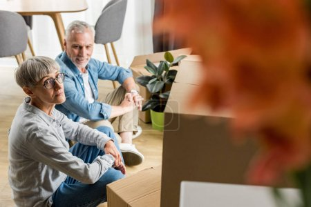 Photo pour Foyer sélectif de l'homme et de la femme mûrs assis sur le sol dans une nouvelle maison - image libre de droit
