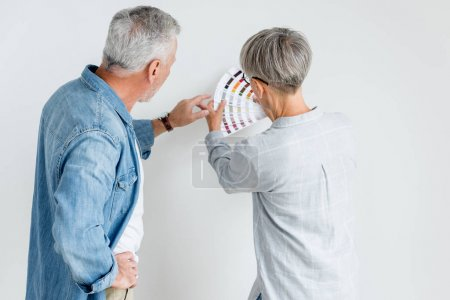 Photo pour Vue arrière de l'homme mature pointant du doigt la palette et la femme la tenant dans une maison neuve - image libre de droit