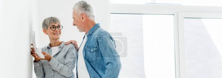 Photo for Panoramic shot of smiling man looking at mature woman with palette in new house - Royalty Free Image