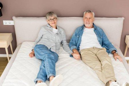 Photo pour Homme mature et femme souriante tenant la main dans le lit dans une nouvelle maison - image libre de droit