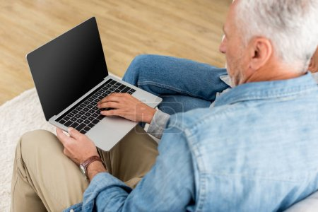 cropped view of mature man and woman using laptop in new house