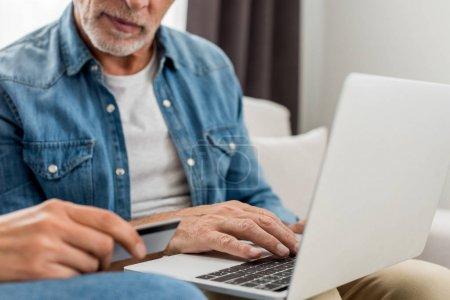 Photo pour Crochet vue d'un homme adulte tenant un ordinateur portable et d'une femme tenant une carte de crédit dans une nouvelle maison - image libre de droit