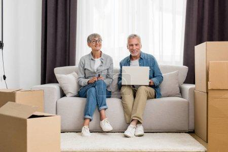 Photo pour Mature homme avec ordinateur portable et femme souriant à la caméra dans une nouvelle maison - image libre de droit