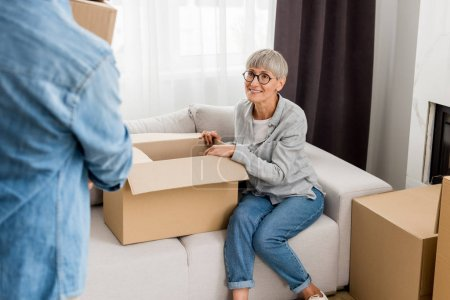 Photo for Cropped view of mature man holding box and smiling woman sitting on sofa in new house - Royalty Free Image