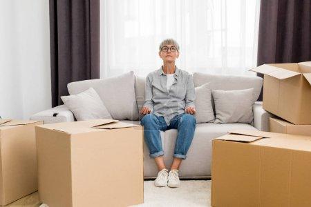 Photo pour Une femme mûre assise sur un canapé et méditant dans une nouvelle maison - image libre de droit