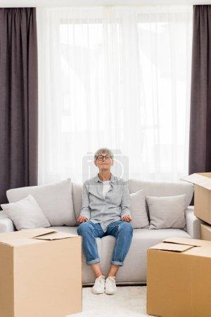 Photo pour Femme mûre avec les yeux fermés assis sur le canapé et méditant dans une nouvelle maison - image libre de droit