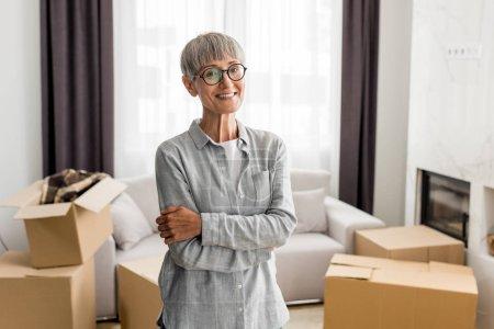 Photo pour Femme souriante avec les bras croisés regardant caméra dans une nouvelle maison - image libre de droit