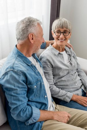 Photo pour Mature homme étreignant femme souriante et assis sur canapé dans nouvelle maison - image libre de droit