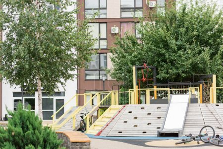 Photo for Playground, bike and plants near new building - Royalty Free Image