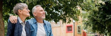 Photo pour Plan panoramique de mature homme étreignant femme souriante et détournant les yeux - image libre de droit