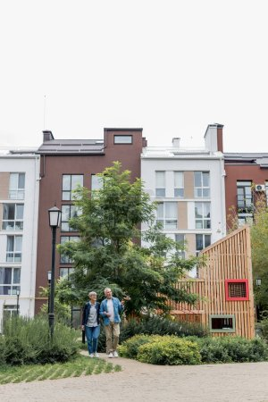 Photo for Mature man and woman walking near new buildings outside - Royalty Free Image
