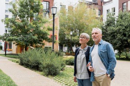 Photo pour Homme mûr et femme souriante regardant loin près des nouveaux bâtiments - image libre de droit