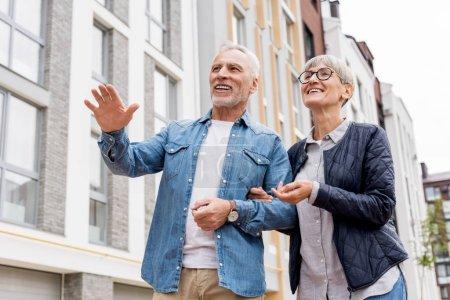 Photo pour Vue à angle bas de l'homme mûr et de la femme souriante regardant loin près de nouveaux bâtiments - image libre de droit