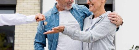 Photo pour Photo panoramique d'un courtier donnant les clés d'une nouvelle maison à un homme et une femme souriants - image libre de droit
