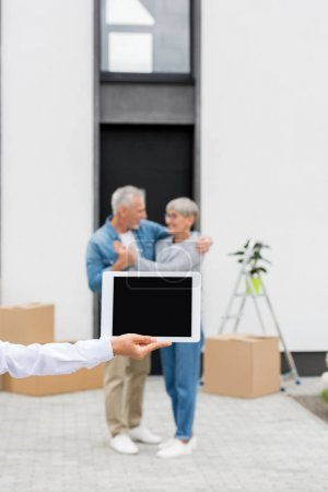 Photo for Selective focus of broker holding digital tablet and couple standing near new house on background - Royalty Free Image
