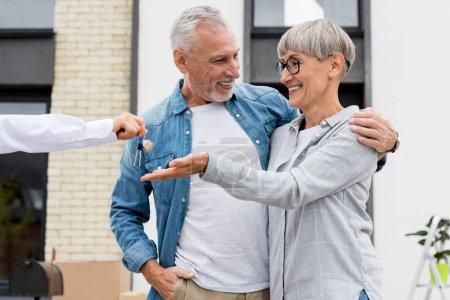 Photo pour Crochet vue d'un courtier donnant les clés d'une nouvelle maison à un homme et une femme souriants - image libre de droit