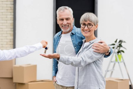 Photo for Cropped view of broker giving keys of new house to smiling man and woman - Royalty Free Image