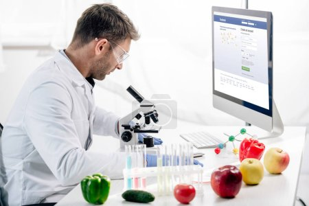 Photo for KYIV, UKRAINE - OCTOBER 4, 2019: side view of molecular nutritionist using computer with facebook website - Royalty Free Image