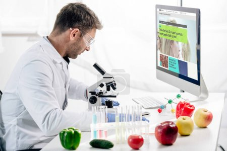 Photo for KYIV, UKRAINE - OCTOBER 4, 2019: side view of molecular nutritionist using computer with bbc website - Royalty Free Image