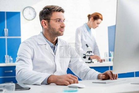 Photo pour Focalisation sélective du nutritionniste moléculaire à l'aide d'un ordinateur et son collègue utilisant le microscope à l'arrière-plan - image libre de droit