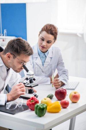 Photo pour Nutritionniste moléculaire utilisant un microscope et son collègue tenant une éprouvette - image libre de droit
