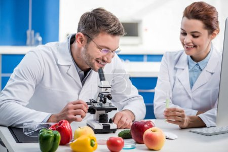 smiling molecular nutritionist using microscope and his colleague holding test tube
