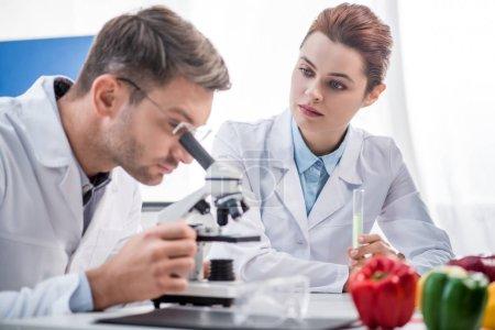 Photo pour Foyer sélectif du nutritionniste moléculaire tenant une éprouvette et regardant son collègue au microscope - image libre de droit