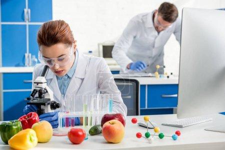 Photo pour Foyer sélectif de nutritionniste moléculaire en utilisant le microscope et collègue sur fond - image libre de droit