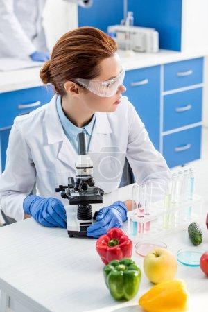 Photo pour Nutritionniste moléculaire assis à table et regardant loin dans le laboratoire - image libre de droit