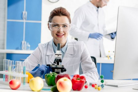 selective focus of smiling molecular nutritionist looking at camera