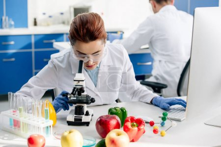 molecular nutritionist in white coat using microscope in lab
