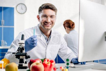 Photo pour Mise au point sélective d'un nutritionniste moléculaire souriant tenant une éprouvette - image libre de droit