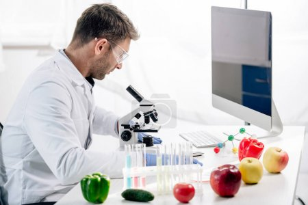 Photo for Side view of molecular nutritionist using microscope in lab - Royalty Free Image