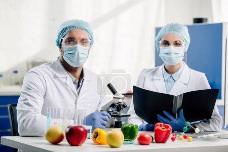 Foto de Nutricionistas moleculares en máscaras médicas mirando a cámara en laboratorio. - Imagen libre de derechos