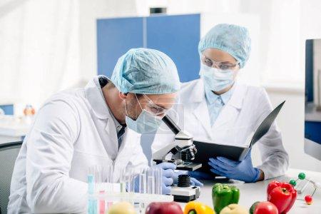 Photo pour Nutritionniste moléculaire tenant dossier et regardant collègue avec microscope - image libre de droit