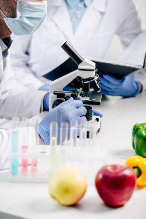Photo pour Foyer sélectif de nutritionniste moléculaire à l'aide d'un microscope et collègue tenant dossier sur fond - image libre de droit
