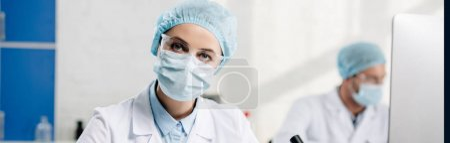 Foto de Foto panorámica de consultor genético mirando cámara en laboratorio - Imagen libre de derechos