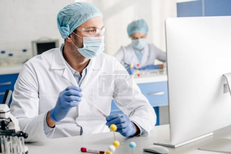 Photo for Selective focus of genetic consultant doing dna test and looking at computer in lab - Royalty Free Image
