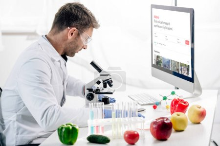 Photo for KYIV, UKRAINE - OCTOBER 4, 2019: side view of molecular nutritionist using computer with airbnb - Royalty Free Image