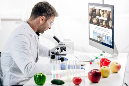 Photo for KYIV, UKRAINE - OCTOBER 4, 2019: side view of molecular nutritionist using computer with depositphotos website - Royalty Free Image