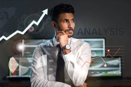 pensive bi-racial trader looking away near charts, graphs and letters in office