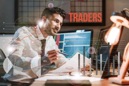 Photo for Happy bi-racial man holding paper near computer with graphs and traders letters - Royalty Free Image