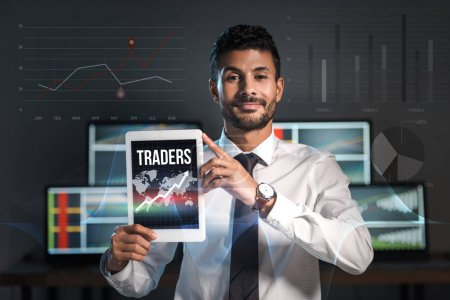 Photo for Happy bi-racial man holding digital tablet with traders letters - Royalty Free Image