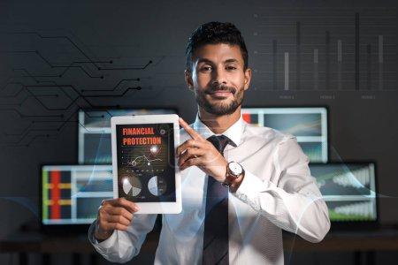 Photo pour Happy bi-racial trader holding digital tablet with financial protection letters - image libre de droit