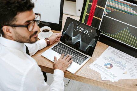 Photo pour Selective focus of bi-racial trader using laptop with forex letters - image libre de droit