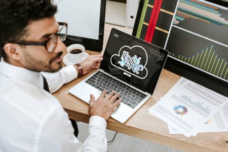 selective focus of bi-racial trader using laptop with login letters