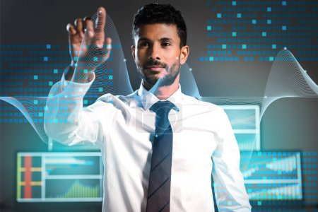 Photo for Selective focus of bi-racial trader pointing with finger near computers on background - Royalty Free Image