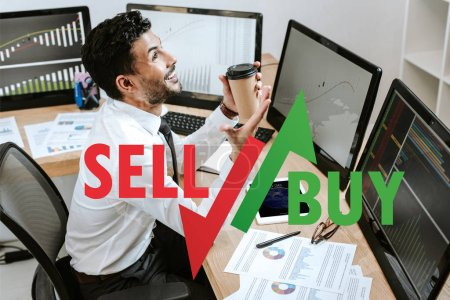Photo for Happy bi-racial trader holding paper cup and sitting near computers and sell, buy letters - Royalty Free Image